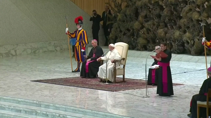 Pope chuckles as small mute boy tugs on Swiss guard sleeve during audience
